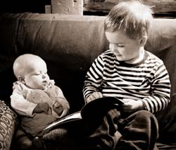 Brother reading to baby